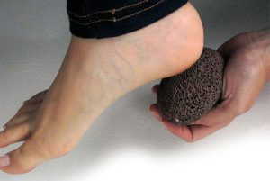 picture of foot being scrubbed by pumice stone